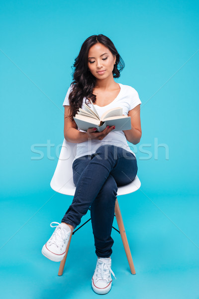 Pensive young vietnamese girl reading book and sitting on chair Stock photo © deandrobot