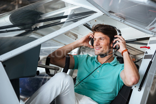 Smiling man pilot sitting in cabin of small aircraft Stock photo © deandrobot