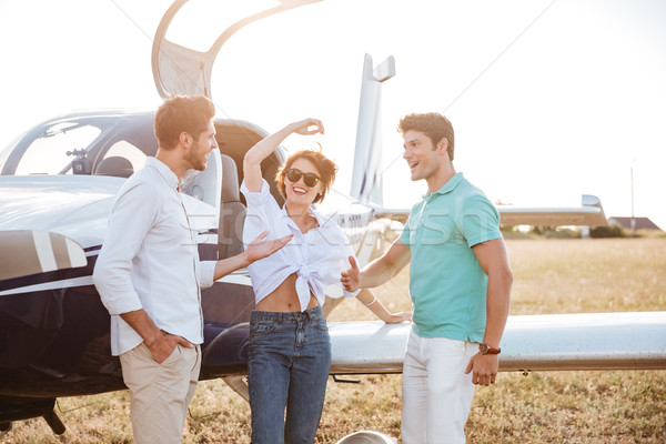 Cheerful young friends standing and talking on runway near airplane Stock photo © deandrobot