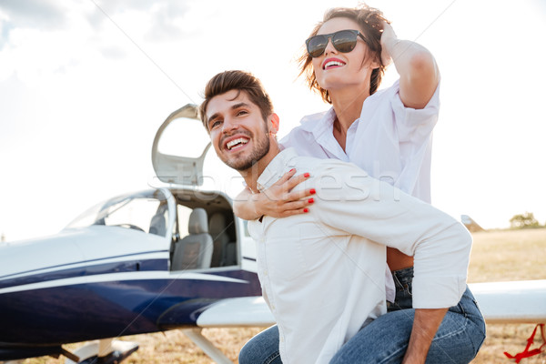 Couple laughing and having fun on runway near private plane Stock photo © deandrobot