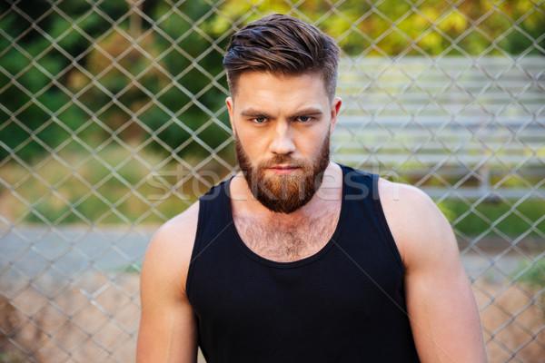 Concentrato barbuto uomo tshirt guardando fotocamera Foto d'archivio © deandrobot