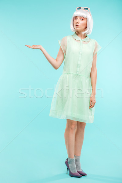 Beautiful young woman in blonde wig holding copyspace on palm Stock photo © deandrobot