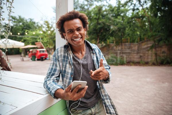 Photo stock: Africaine · jeune · homme · écouter · de · la · musique · téléphone · portable · rire