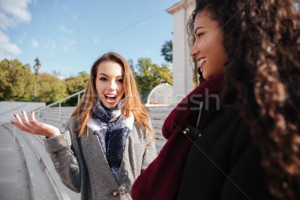 Happy ladies over street background. Focus on caucasian surprised woman Stock photo © deandrobot