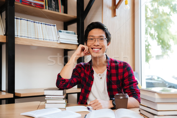 Asian man sitting with books at the library Stock photo © deandrobot
