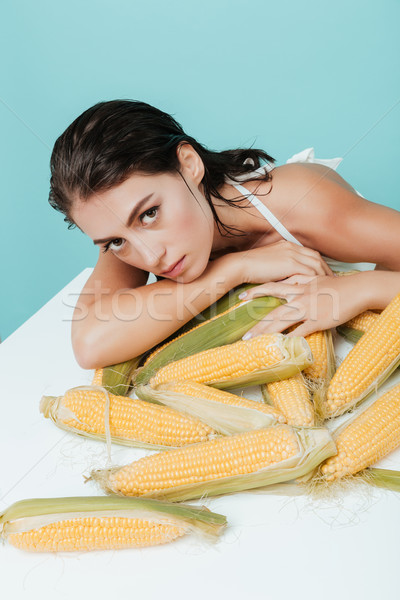 Beautiful young woman leaning on the table with corn cobs Stock photo © deandrobot