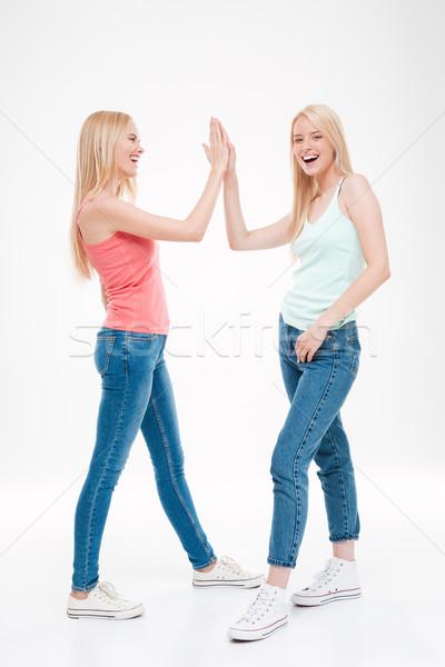 Deux jeunes femmes high five photo jeans isolé Photo stock © deandrobot