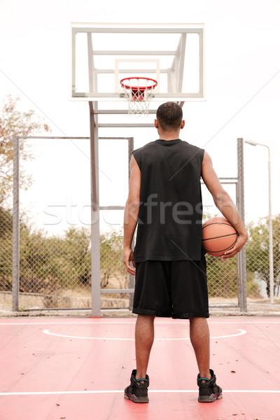 Hátulnézet kosárlabdázó áll tart labda hátsó nézet Stock fotó © deandrobot