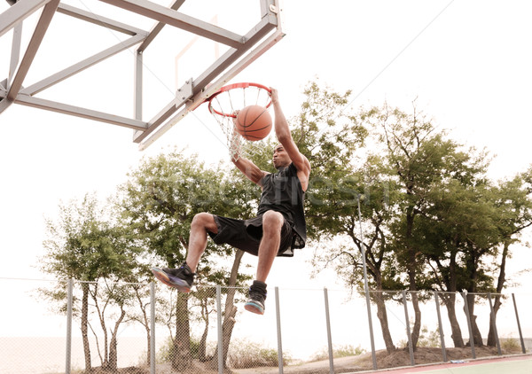 Basketball player practicing and jumping to hoop Stock photo © deandrobot