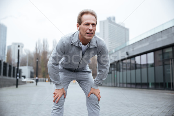 Tired Elderly runner on the street Stock photo © deandrobot