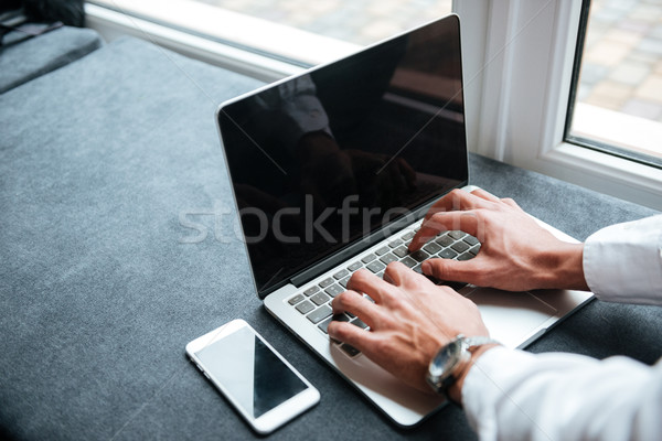 Cropped picture of handsome african businessman typing by laptop computer. Stock photo © deandrobot