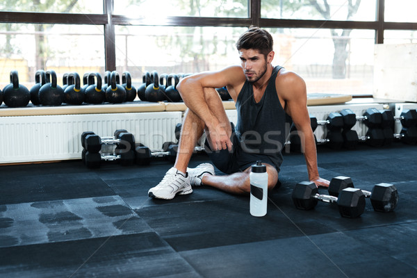 Fitness man sitting down in gym Stock photo © deandrobot