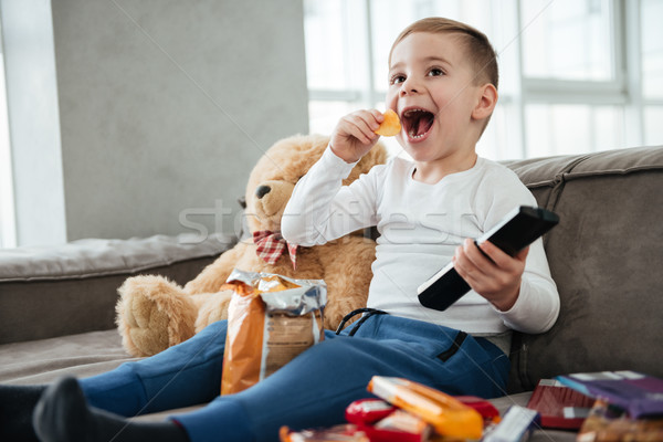 Happy boy sitting on sofa with teddy bear at home Stock photo © deandrobot