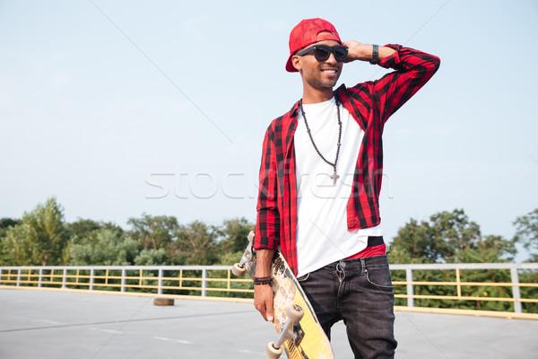 Foto stock: Escuro · homem · óculos · de · sol · andar · de · skate