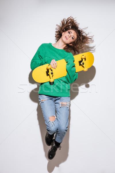 Stock fotó: Fiatal · nő · fehér · gördeszka · ugrik · fotó · görkorcsolyázó