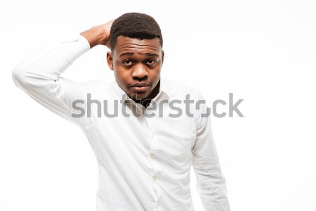 Stock photo: Thinkful young african man dressed in shirt standing isolated
