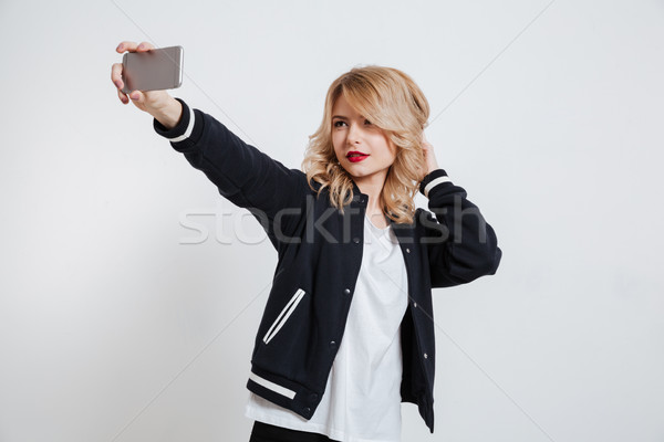 Attractive young girl in casual clothes taking selfie Stock photo © deandrobot