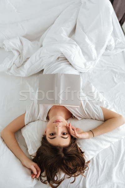 Fiatal csinos nő hazugságok ágy tart könyv Stock fotó © deandrobot