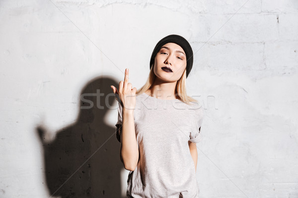 Stylish woman with black lipstick standing and showing middle finger Stock photo © deandrobot