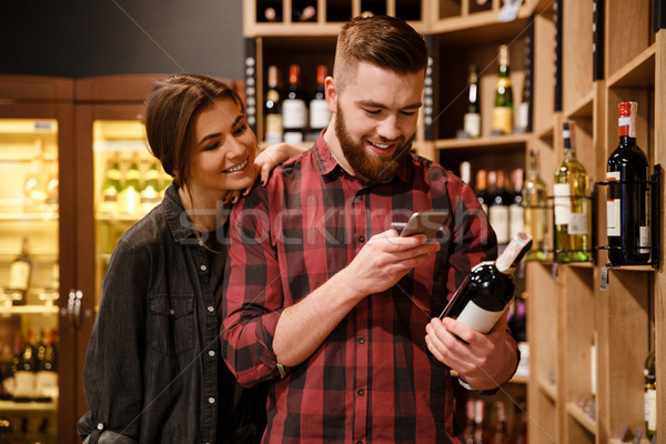 Concentrated loving couple in supermarket choosing alcohol. Stock photo © deandrobot