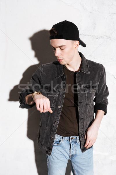 Man standing on floor looking at watch Stock photo © deandrobot