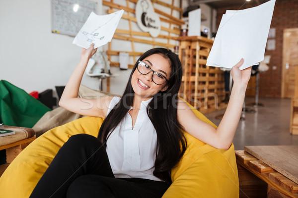 Sorridente asiático mulher jovem documentos sessão saco de feijão Foto stock © deandrobot