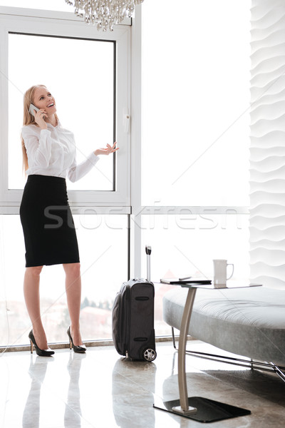 Laughing young business lady in office talking by phone. Stock photo © deandrobot