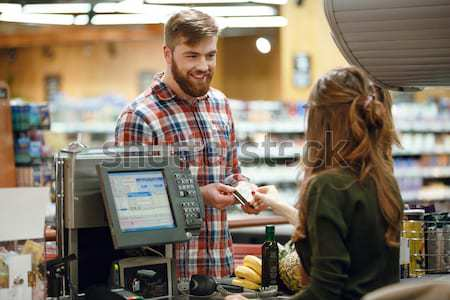 Cheerful young man standing in supermarket shop Stock photo © deandrobot