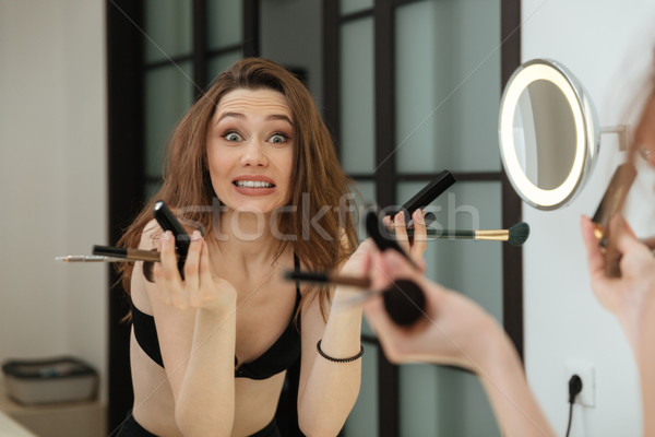 Confused woman holding brushes and doing makeup in bathroom Stock photo © deandrobot