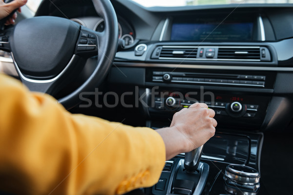 Hand of female driver shifting gear stick before driving car Stock photo © deandrobot