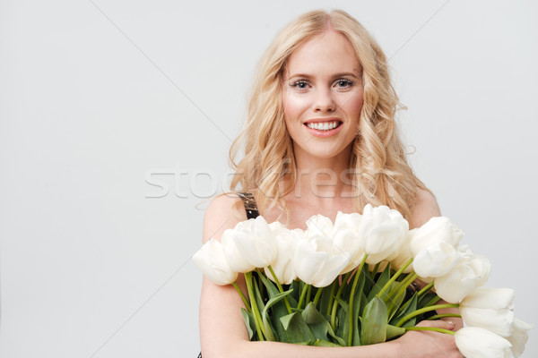 Mosolyog szőke nő tart virágcsokor virágok néz Stock fotó © deandrobot