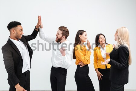 Happy colleagues in office gives a high-five to each other. Stock photo © deandrobot