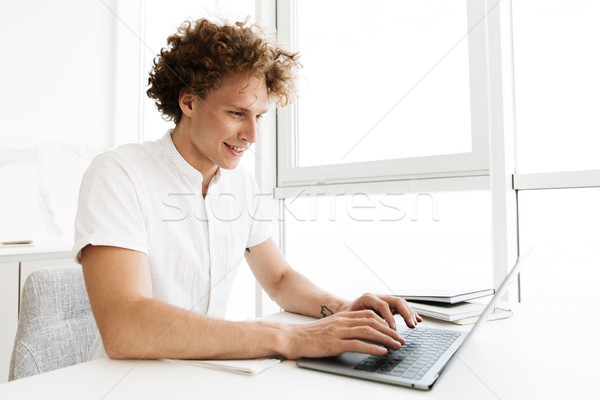 Happy man sitting at the table near window using laptop Stock photo © deandrobot