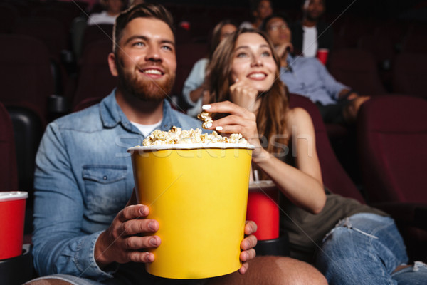 Happy smiling couple holding a big popcorn bucket Stock photo © deandrobot