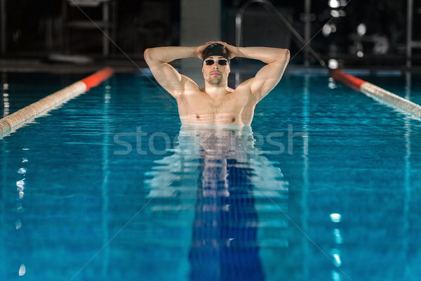 Male swimmer standing in pool Stock photo © deandrobot