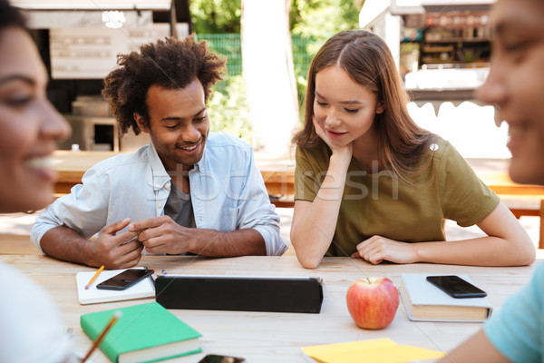 Two young smiling friends sitting outdoors Stock photo © deandrobot