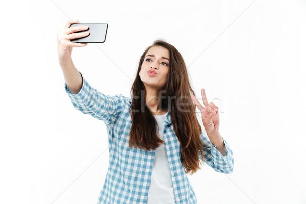 Mooie meisje tonen overwinning gebaar Stockfoto © deandrobot