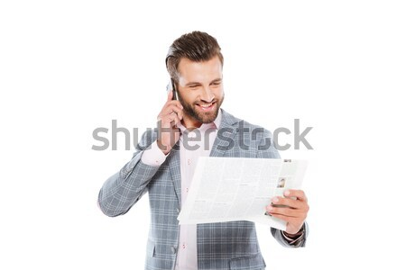 Happy young man holding gazette and talking by mobile phone Stock photo © deandrobot