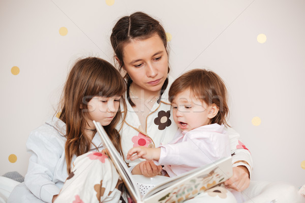 Young woman with daughters reading book Stock photo © deandrobot