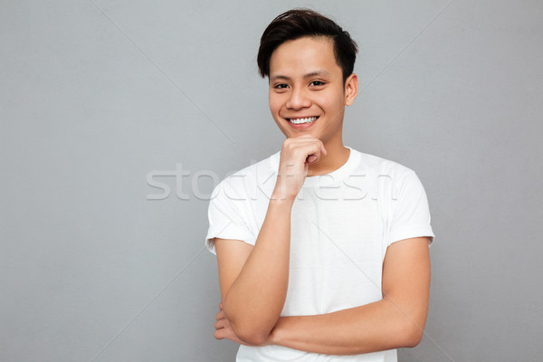 Handsome young asian man standing over grey background Stock photo © deandrobot