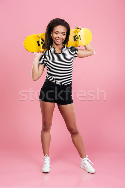 Young smiling african teenage girl standing and holding skateboard Stock photo © deandrobot