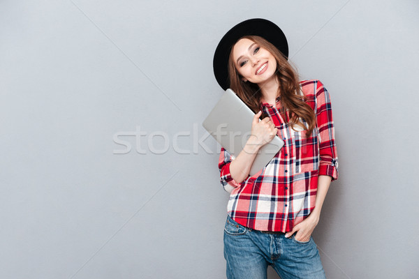 Smiling woman in plaid shirt holding laptop Stock photo © deandrobot
