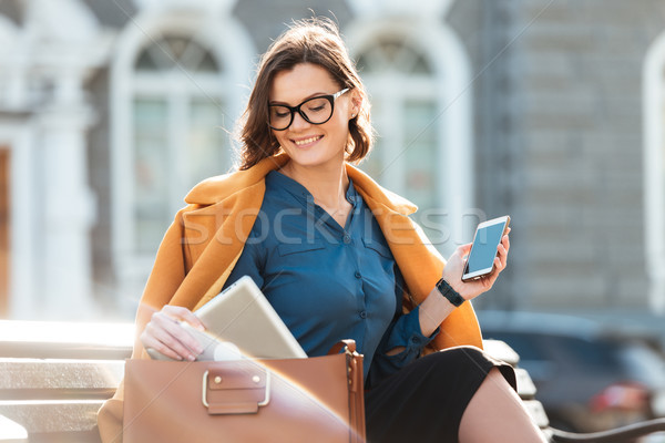 Smiling pretty woman in eyeglasses and coat holding mobile phone Stock photo © deandrobot