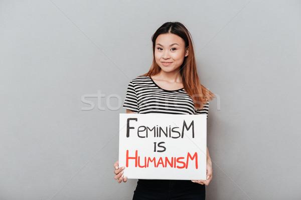 Lächelnd asian Frau halten Plakat Slogan Stock foto © deandrobot