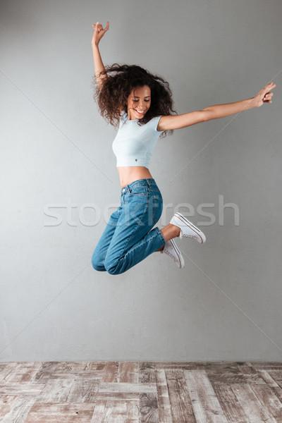 Freudige Frau springen isoliert glücklich Jeans Stock foto © deandrobot