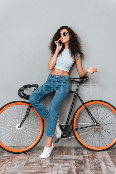 Full length image of smiling curly woman in sunglasses Stock photo © deandrobot