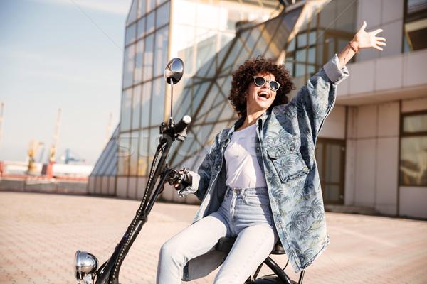 вид сбоку беззаботный девушки Солнцезащитные очки сидят мотоцикле Сток-фото © deandrobot