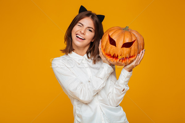 Cute teenage schoolgirl in uniform holding halloween pumpkin Stock photo © deandrobot