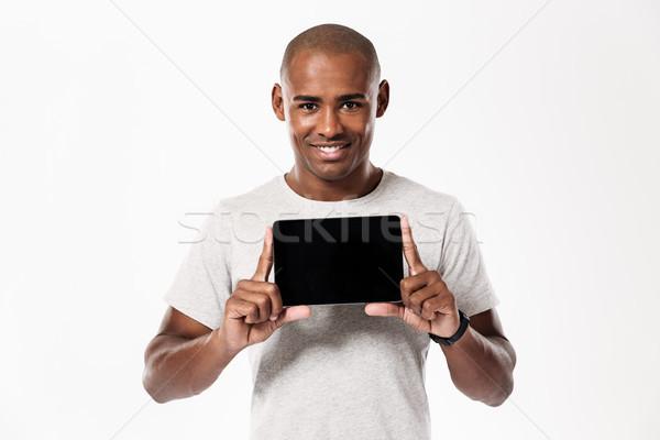 Gelukkig afrikaanse man tonen scherm Stockfoto © deandrobot