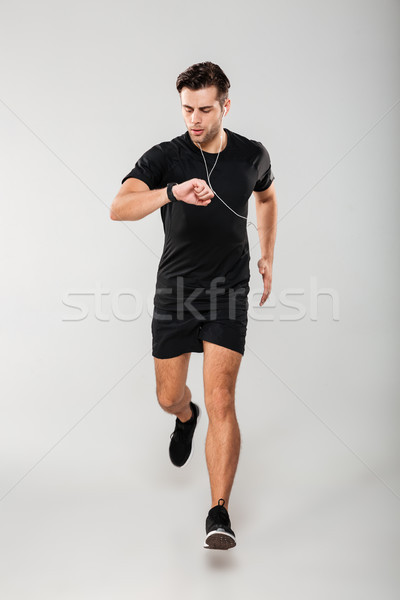 Full length portrait of a young fit sportsman in earphones Stock photo © deandrobot
